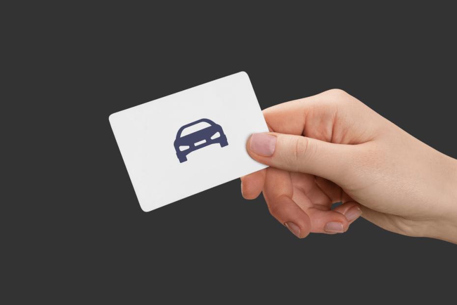 foto de uma mão segurando um cartão de visita com uma ilustração de carro