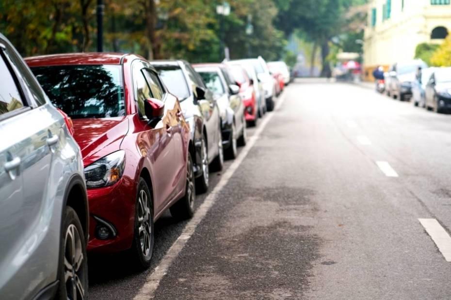 Carros estacionados em fila na lateral de uma rua.