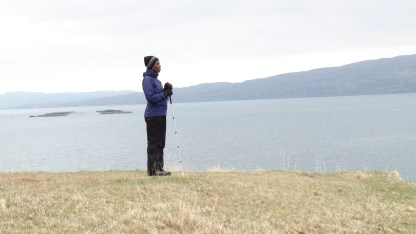 A woman stands, leaning on her white stick, at the edge of a bay.
