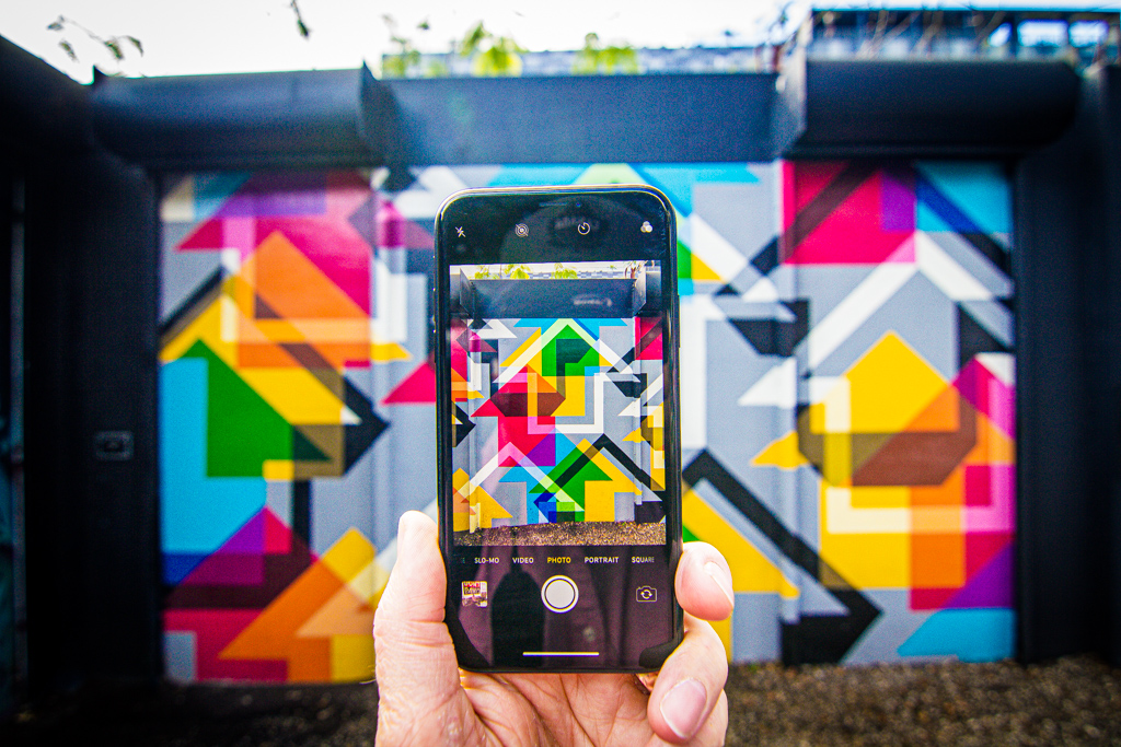 Hand holding a phone taking a photo of graffiti