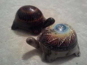 In foreground, a white-grey pottery turtle with rainbow-painted etched shell (Tom Vail Jr.); in background, a black clay turtle in foreground (by Johnny Williams).