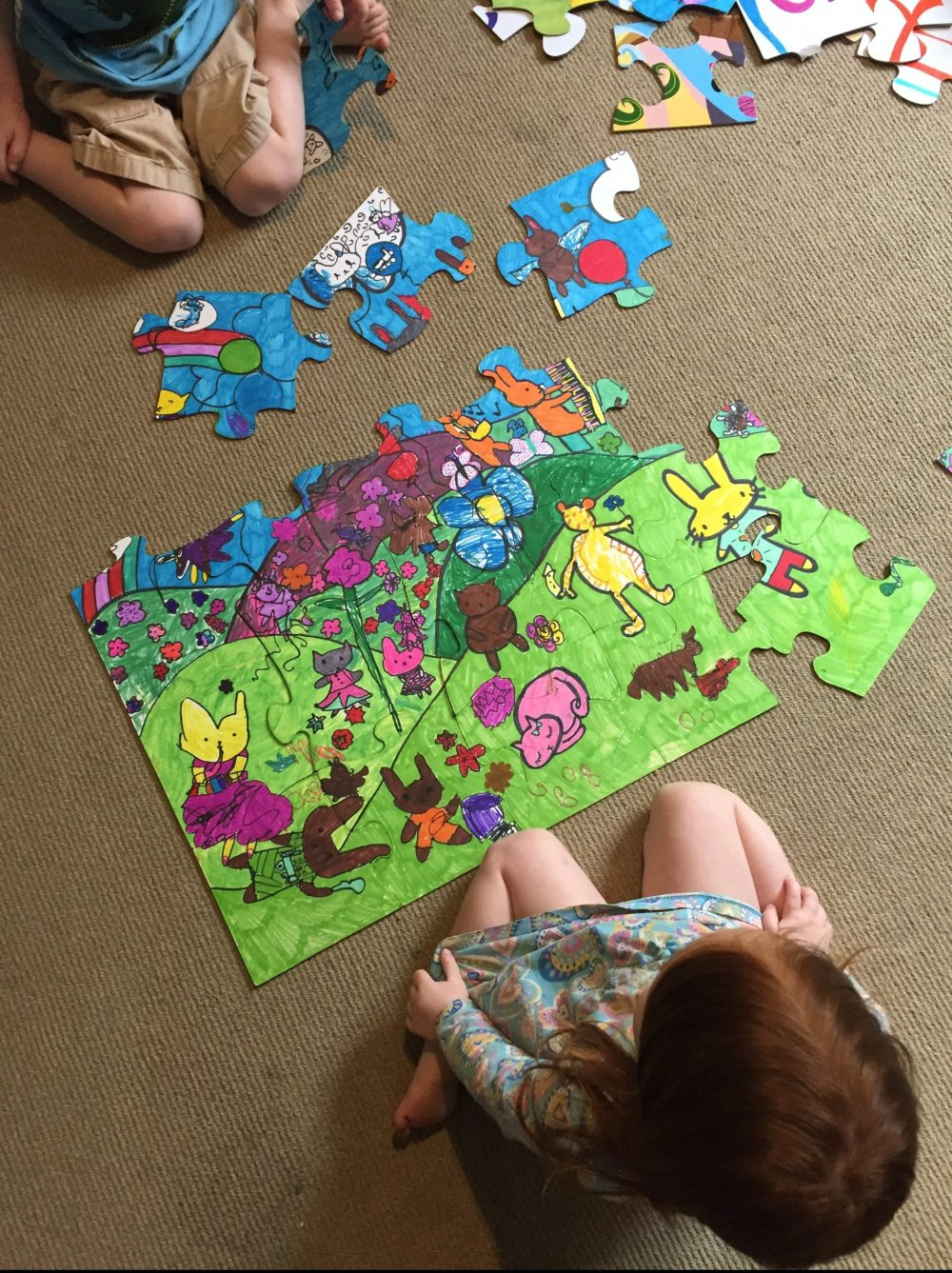 Children making a hand-drawn puzzle on the back of another puzzle, Creative Family Idea Box, Creative Family Culture and the Sacred Everyday by Mackenzie Chester