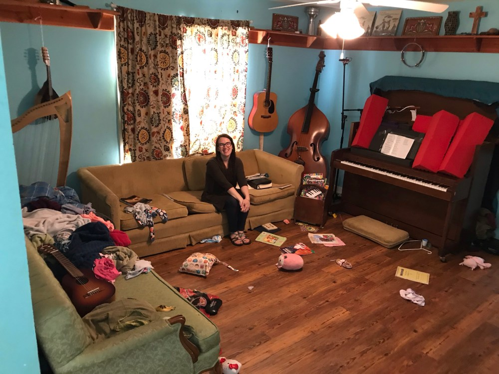 mom in messy living room, smiling, making peace with the mess