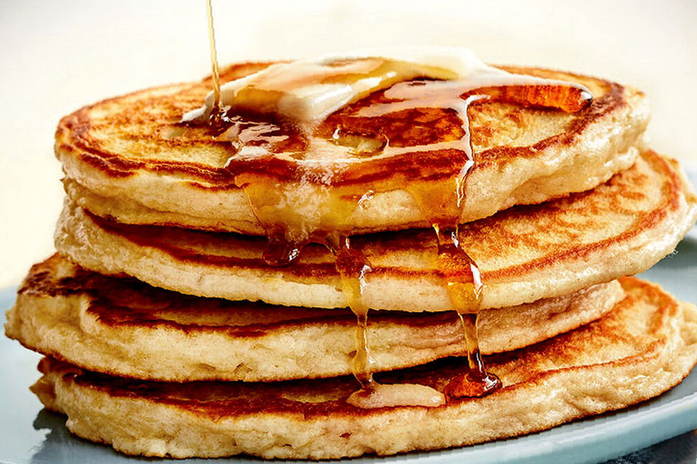 maple syrup being drizzled over stack of pancakes with butter