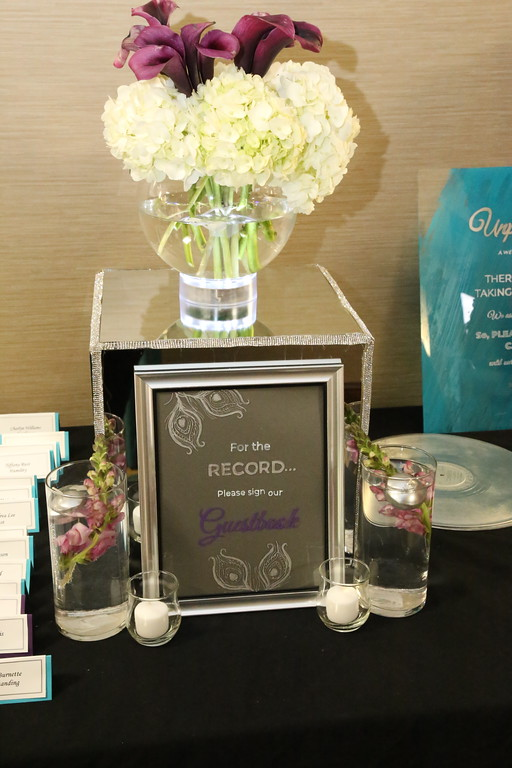Teal and purple escort cards, clear guest book sign with silver frame, white and silver writing.  Glass vases with silver candles and snapdragons.  Silver records.  Teal painted unplugged ceremony sign. Bubble bowl with white hydrangeas and purple calla lilies.
