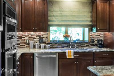 Granite countertop in Neptune Bordeaux with bold tile backsplash