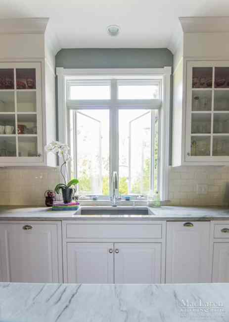 Sea Pearl Quartzite countertops and glass White Cabinetry aligning a gorgeous sink view