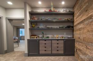 This Basement remodel by MacLaren Kitchen and Bath features a kids room with the ultimate toy storage with floating shelves and open drawers