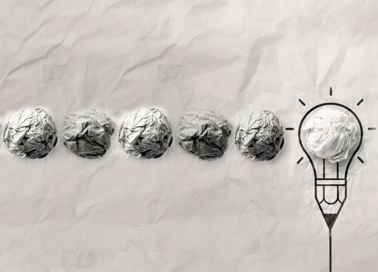 Folhas de papéis amassadas com o desenho de uma lâmpada (ideia) no fim