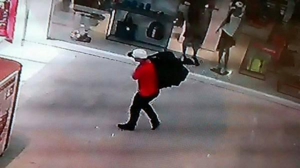 Assaltantes com produtos roubados de uma loja iPlace, no Shopping Pelotas