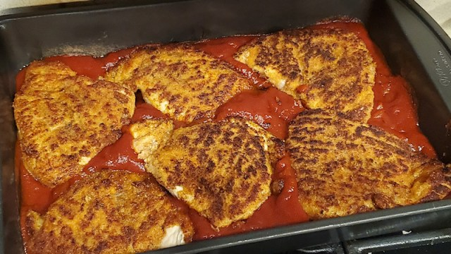 Browned and breaded chicken patties in sauce