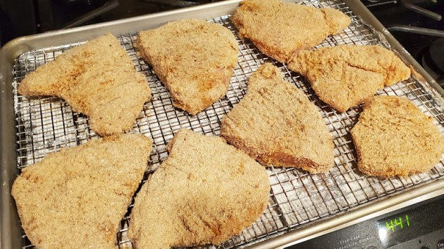 Breaded chicken breast patties drying on a rack