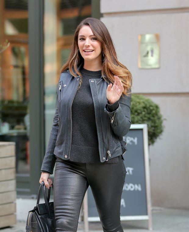 Kelly Brook waves while leaving her hotel in New York City, NY