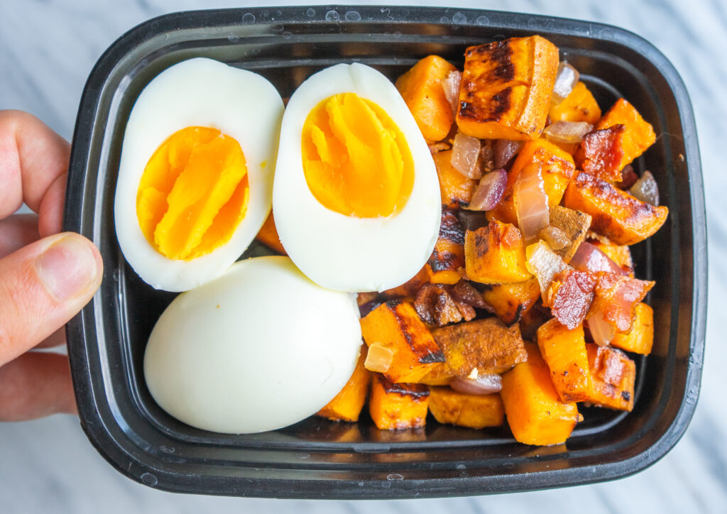 above view of a hand holding a meal prep container with a paleo breakfast inside