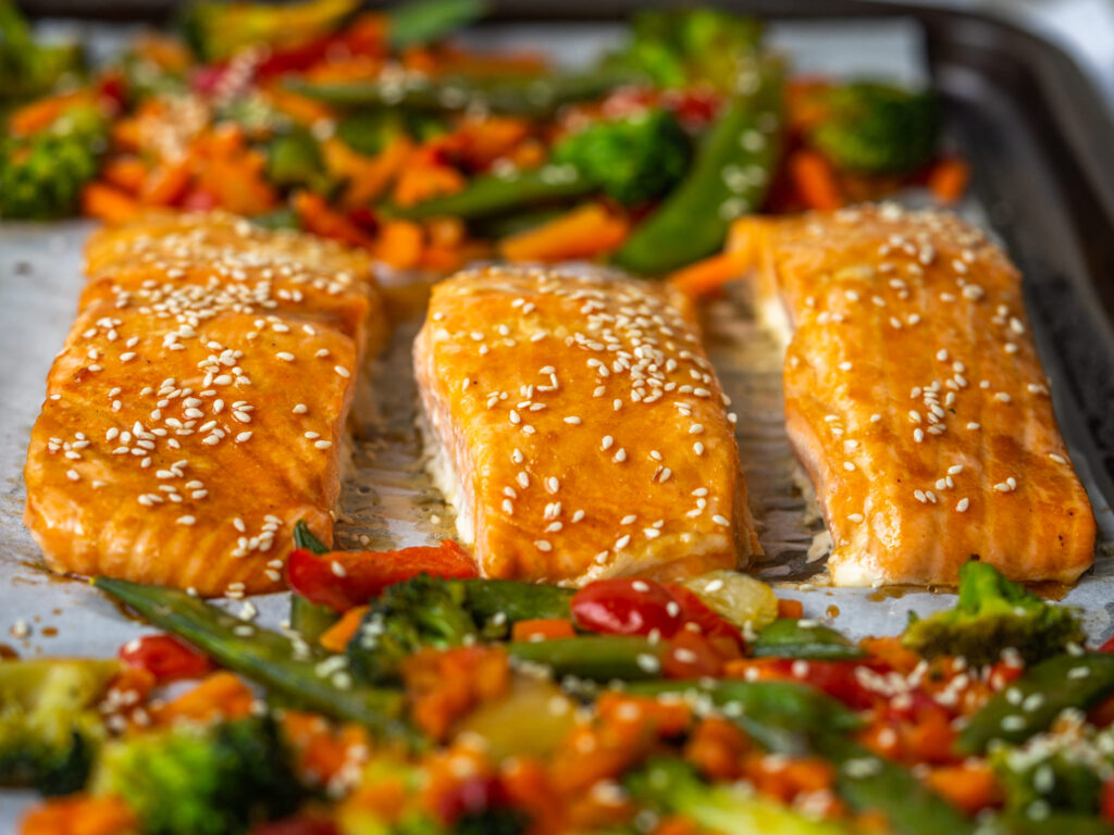 three quarter view of baked salmon filets on a sheet pan with veggies