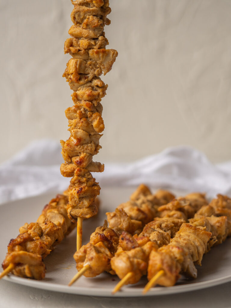 Side view of a  whole30 marinated chicken skewer standing up on a plate