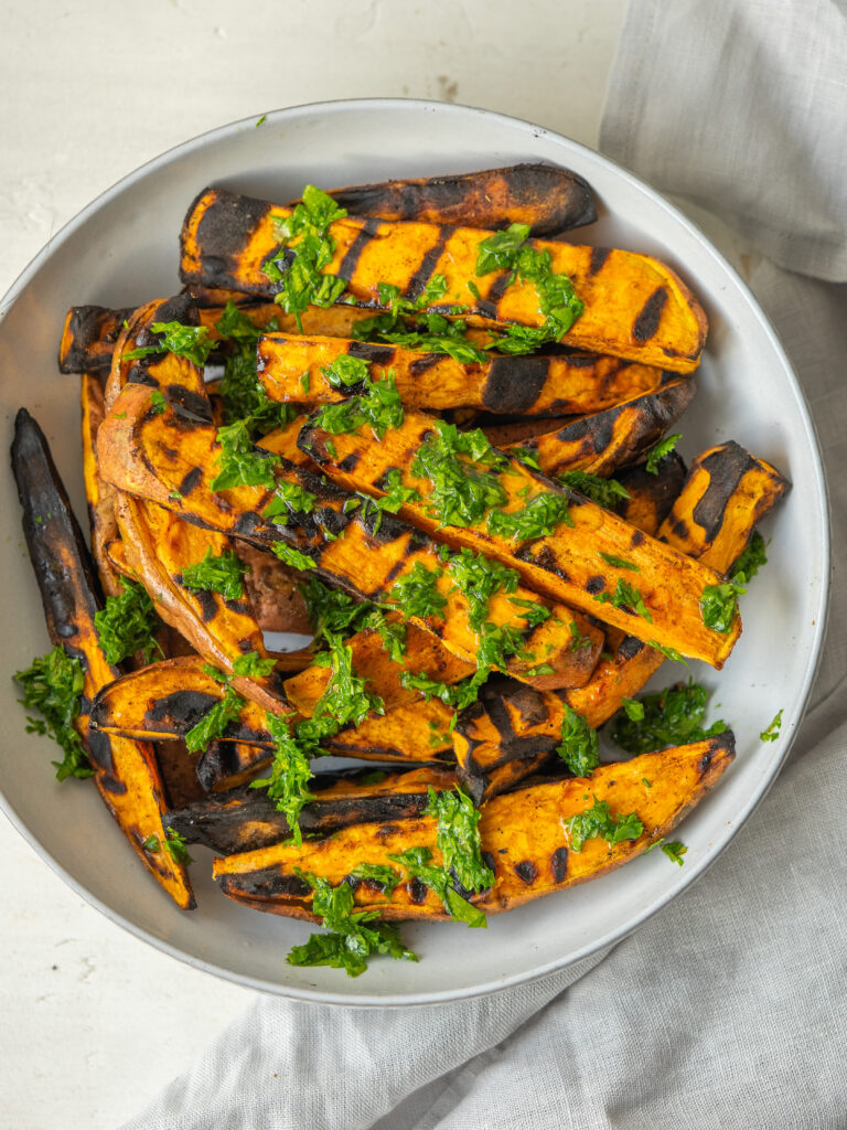 Above view of grilled sweet potatoes on a serving bowl with a mixed herb dressing