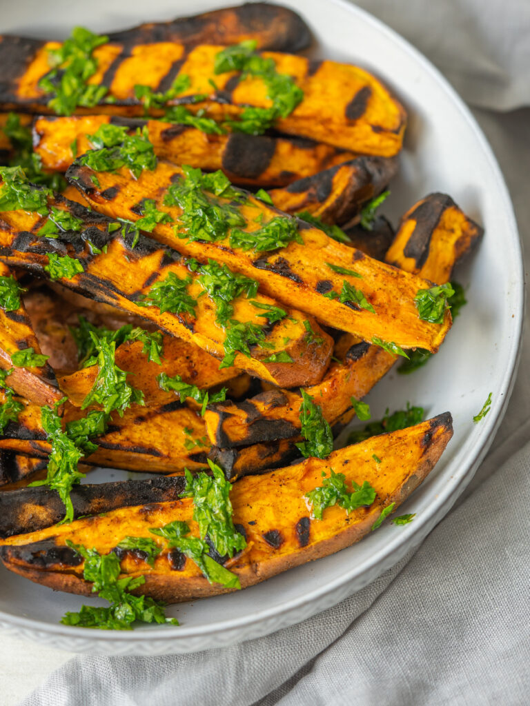 Close up three quarter view of grilled sweet potatoes with a mixed herb dressing