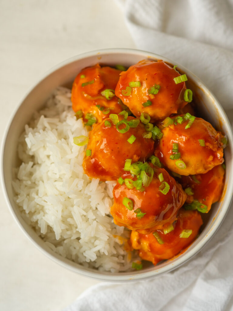 Above view of sweet and sour chicken meatballs in a bowl with white rice