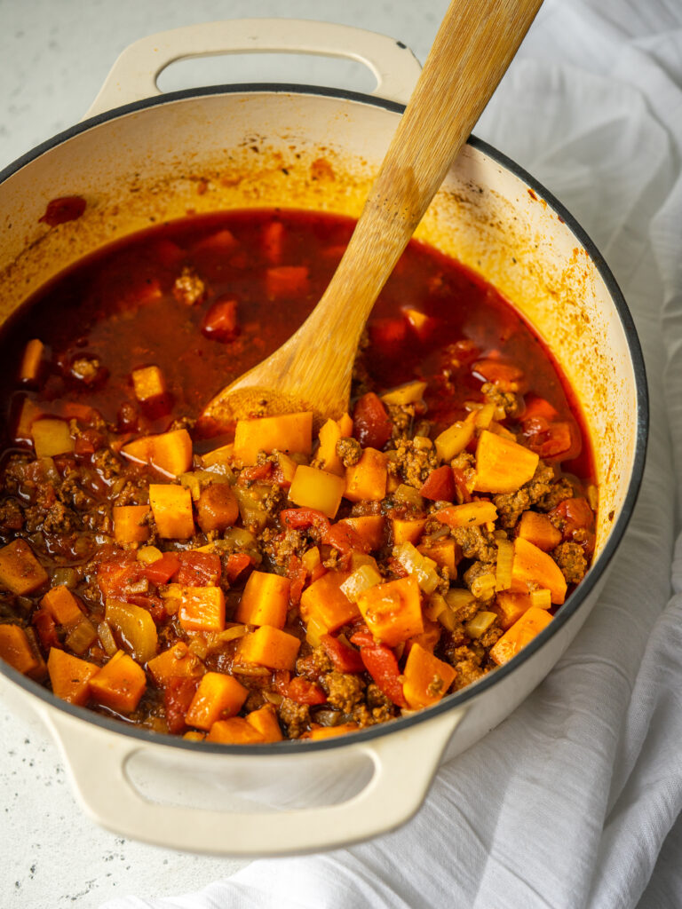 Three quarter view of whole30 chili in a pot with a wooden spoon