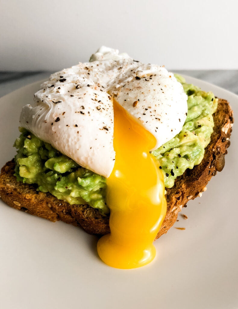 three quarter view of  a perfect poached egg on a piece of avocado toast. The poached egg is sliced open and yolk is coming out.