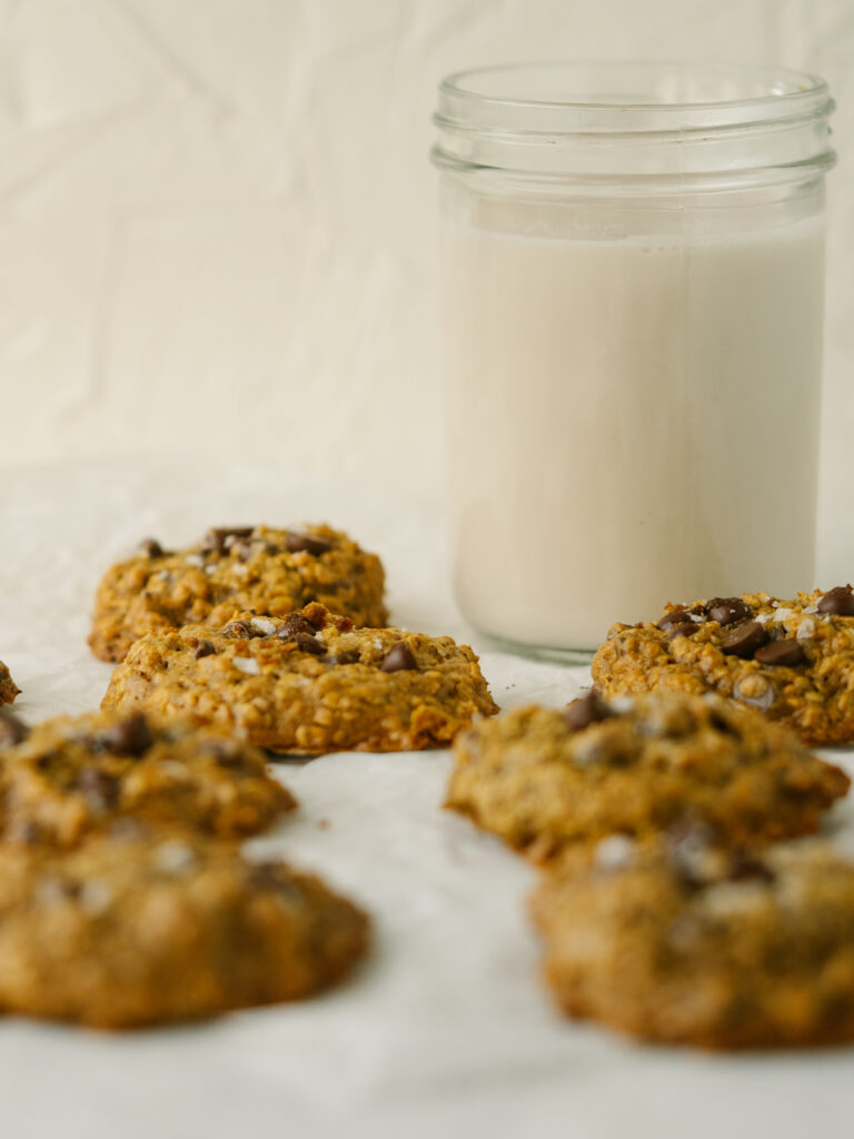 Side view of healthy peanut butter oatmeal cookies on a piece of parchment paper next to a glass of milk