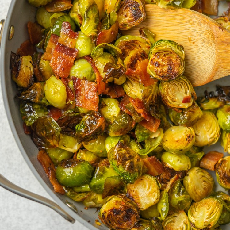 Above view of maple bacon brussels sprouts in a frying pan with a wooden spoon