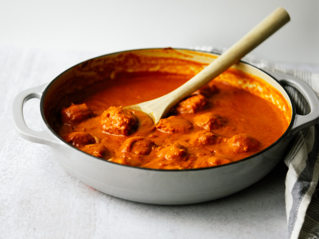 side view of baked chicken meatballs in a tikka masala sauce