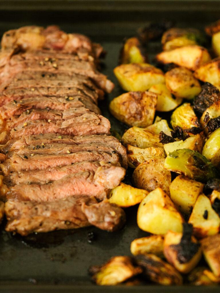 close up of sliced steak on a sheet pan