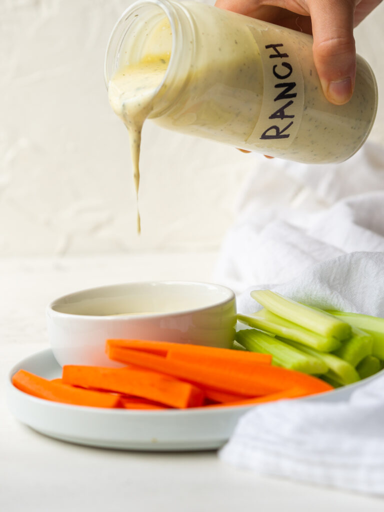 Side view of a homemade Whole30 ranch dressing pouring into a serving dish