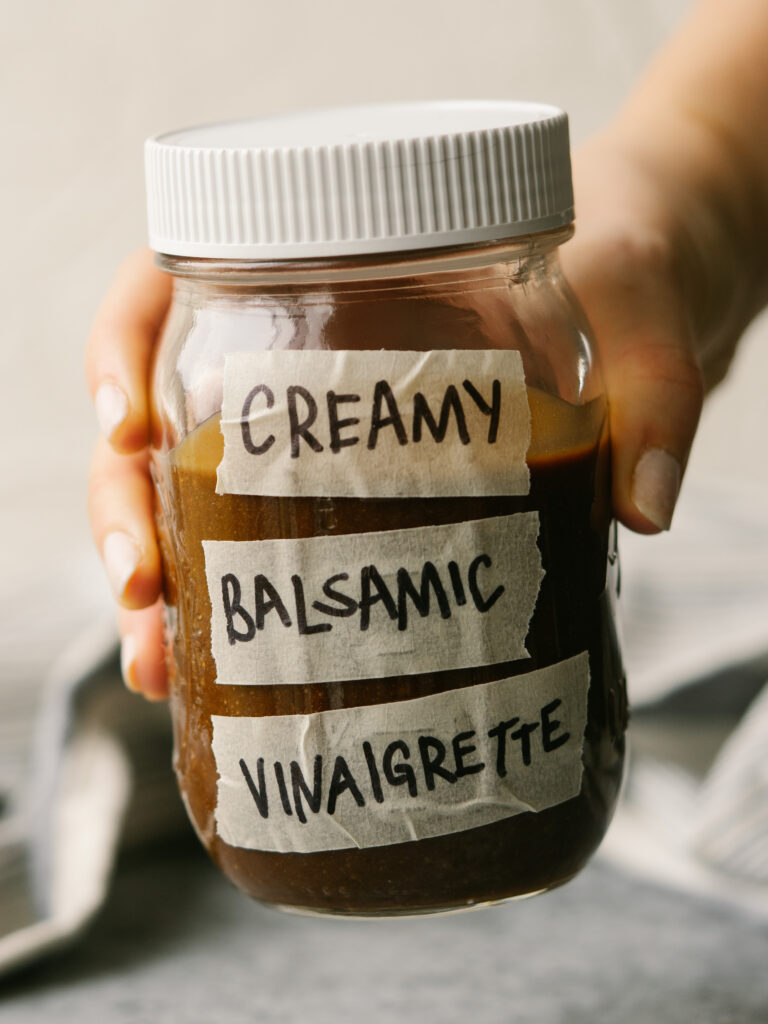 a hand holding balsamic dressing in a jar with a label that says creamy balsamic vinaigrette