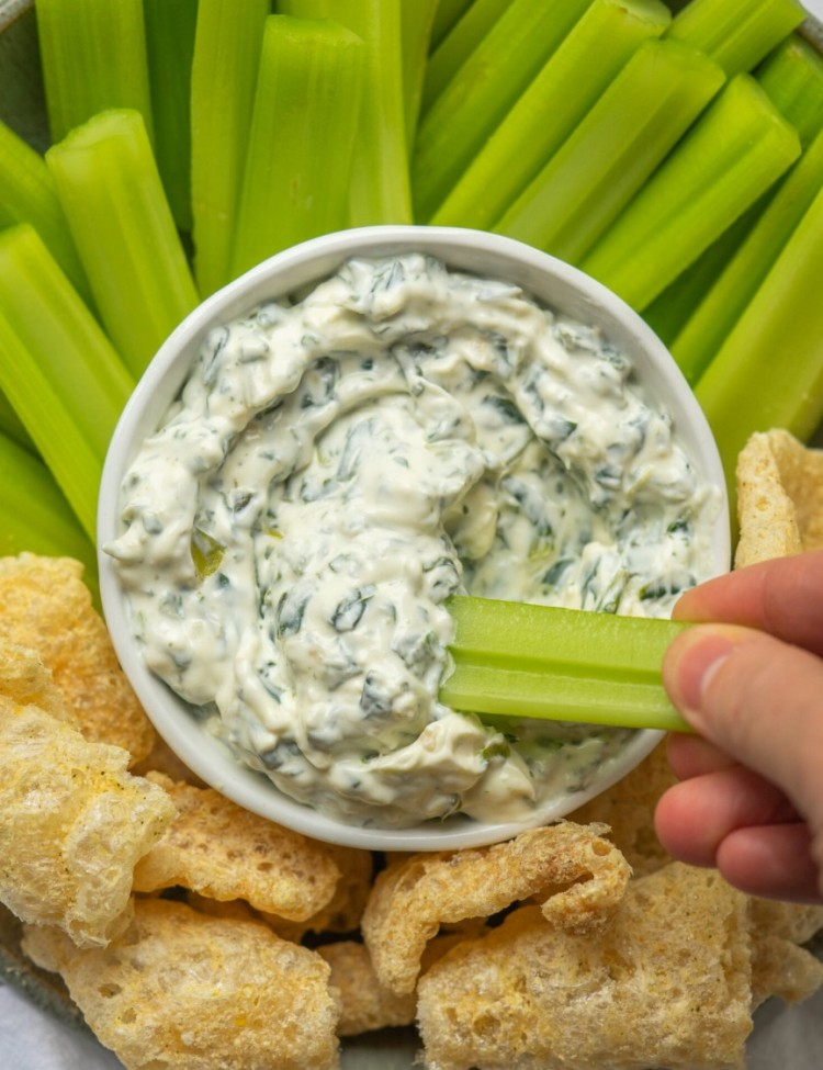 Above view of a piece of celery dipping into an Easy Spinach Dip