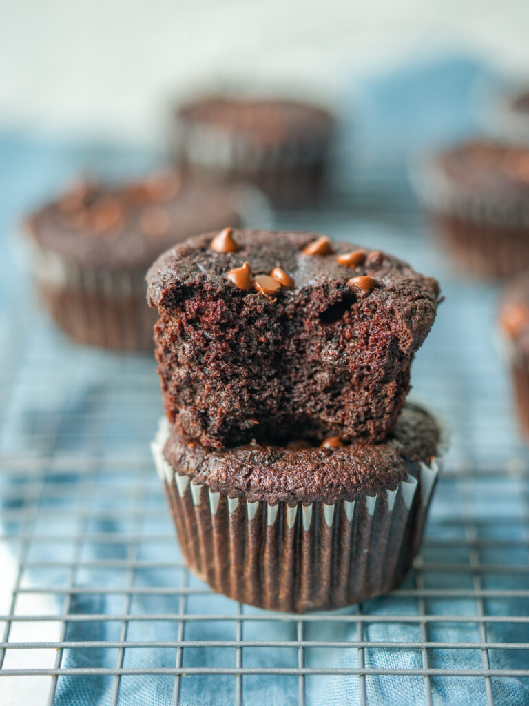 side view of healthy chocolate muffins stacked on  a cooling rack