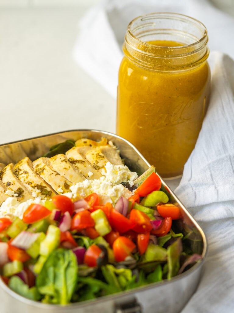 Three quarte view of a salad in a metal lunch container next to a Mason Jar Salad Dressing