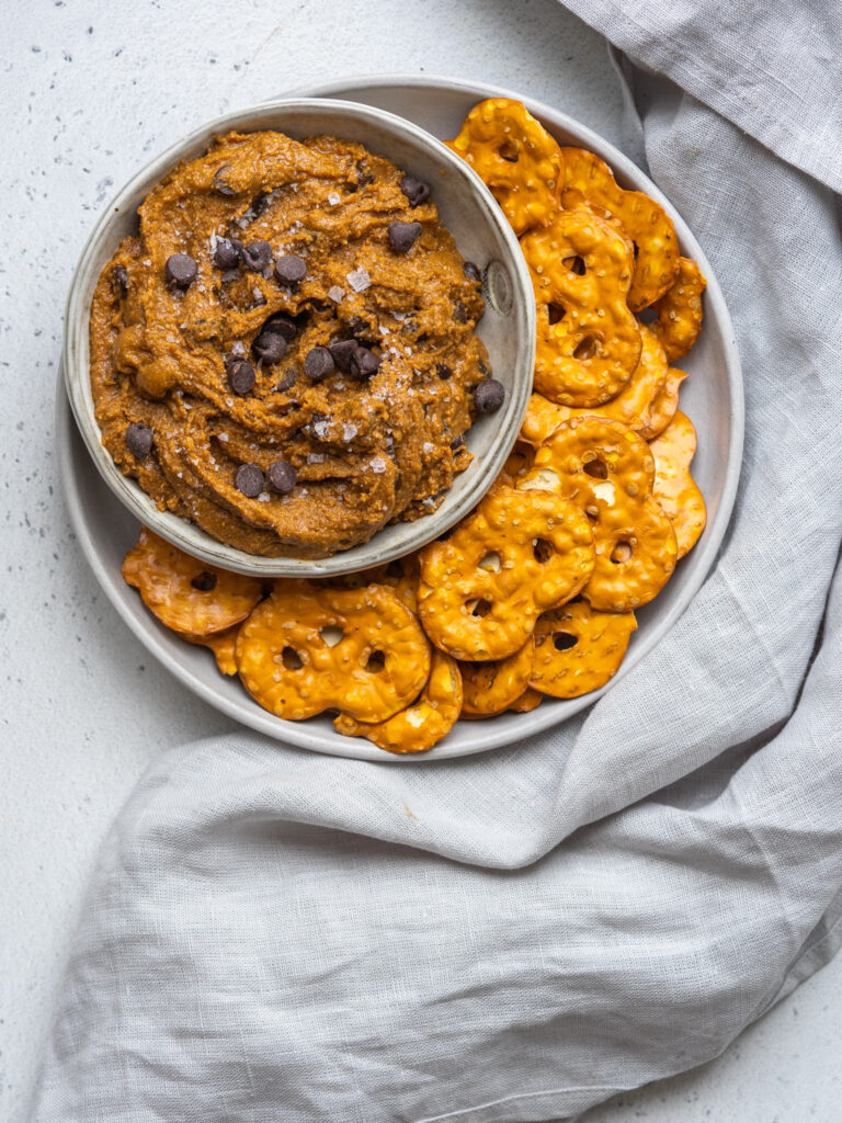 Above view of a chocolate chip cookie dough dip in a serving bowl with pretzel thins on the side