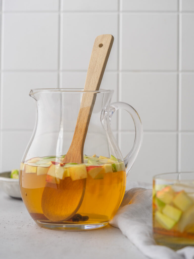 Side view of apple cider sangria recipe in a serving pitcher with a wooden mixing spoon in it