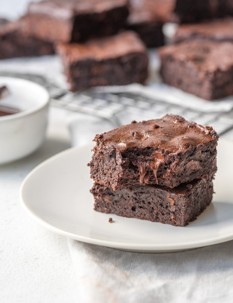Side view of two flourless brownies stacked on top of one another on a serving plate with more double chocolate brownies in the background