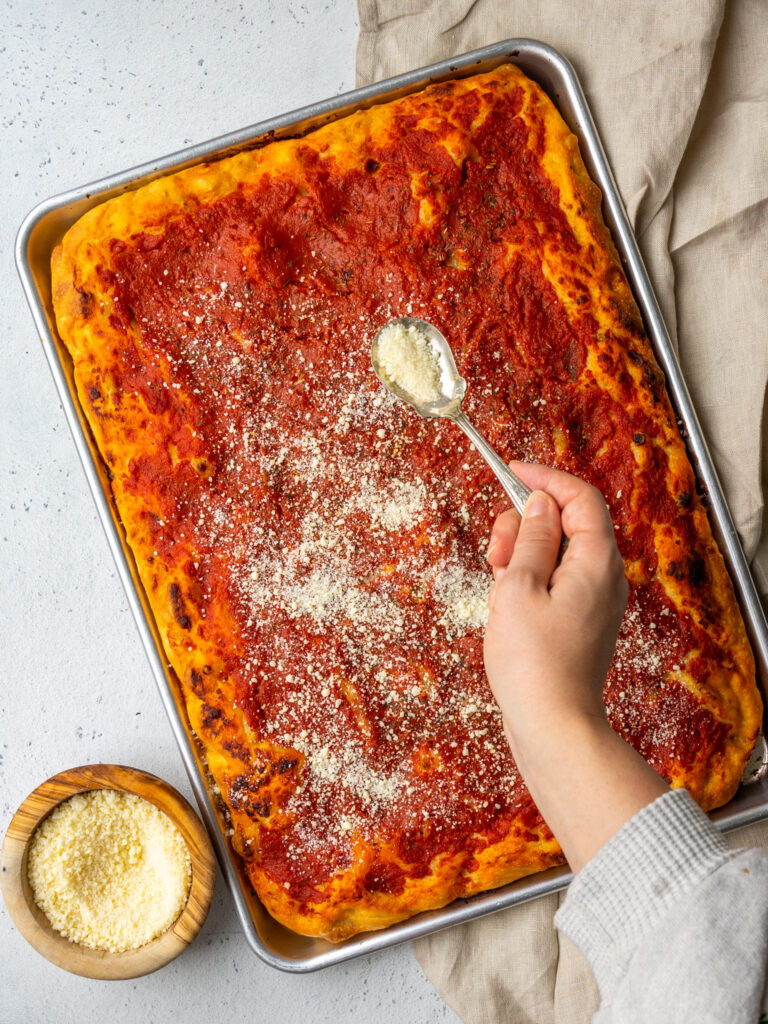 Above view of a hand shaking a spoonful of parmesan cheese over a Philly tomato pie