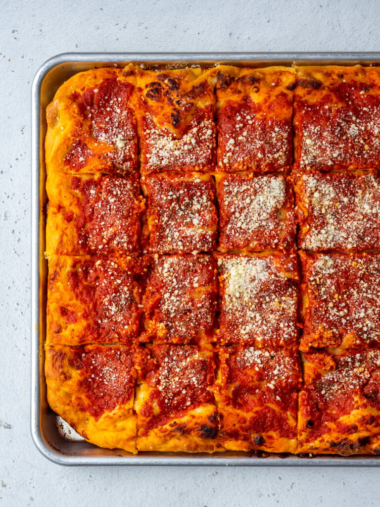 Above view of a sheet pan of Philly tomato pie cut into squares