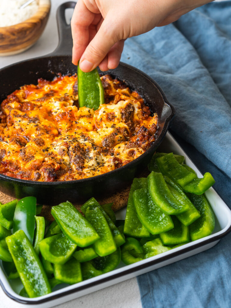 green bell pepper dipping into cast iron skillet