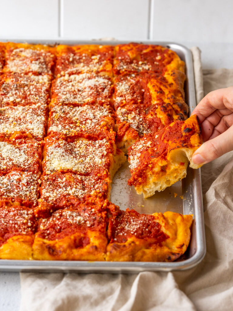 Three quarter view of a hand grabbing a slice of tomato pie pizza