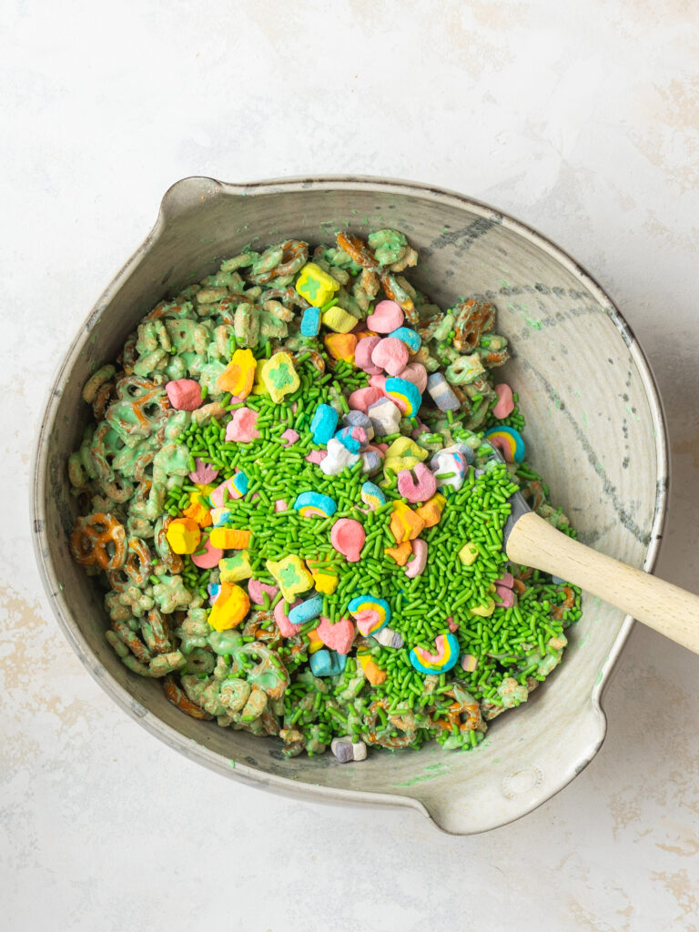 Above view of sprinkles and lucky charm marshmallows being mixed into a sweet snack mix