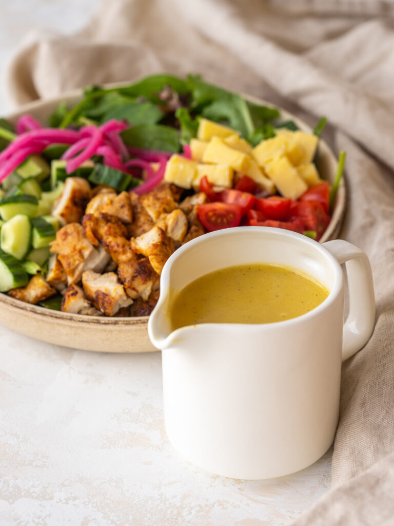 three quarter view of apple cider vinegar salad dressing in a small pitcher in front of a salad