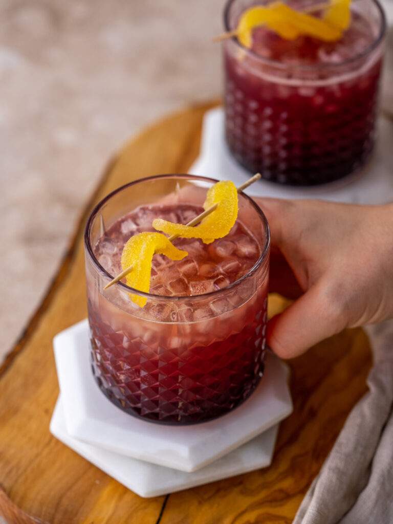 three quarter view of a hand grabbing a cranberry moscow mule in a glass