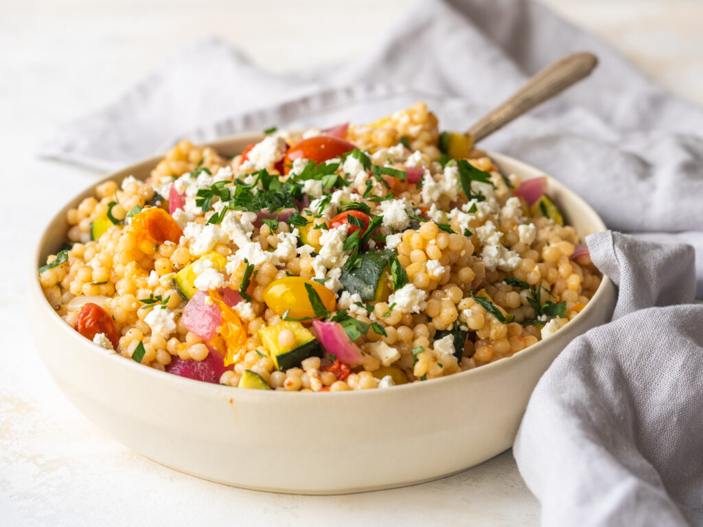 Three quarter view of cooked pearl couscous with roasted veggies