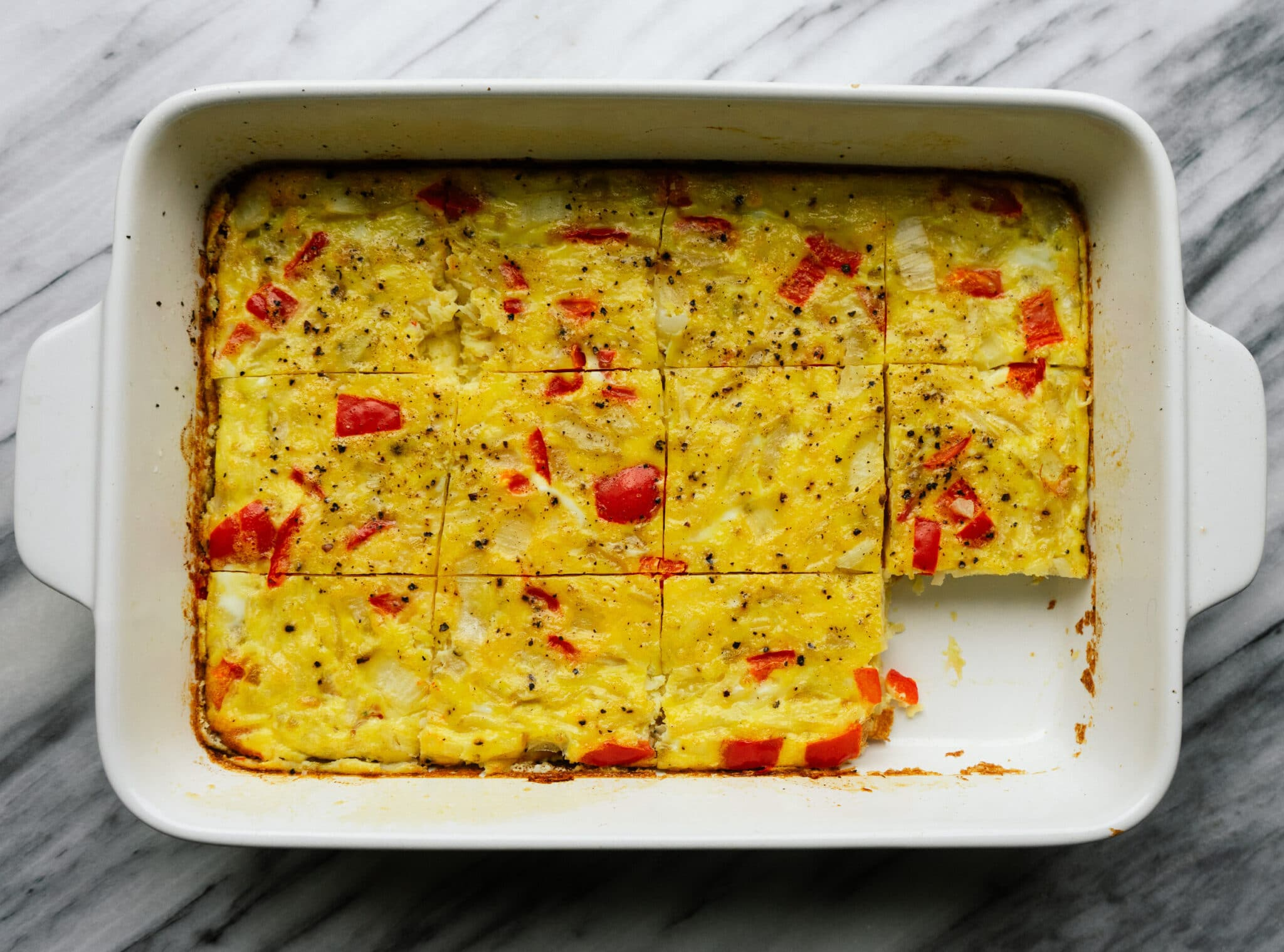 Above view of breakfast casserole with hashbrowns in a baking dish
