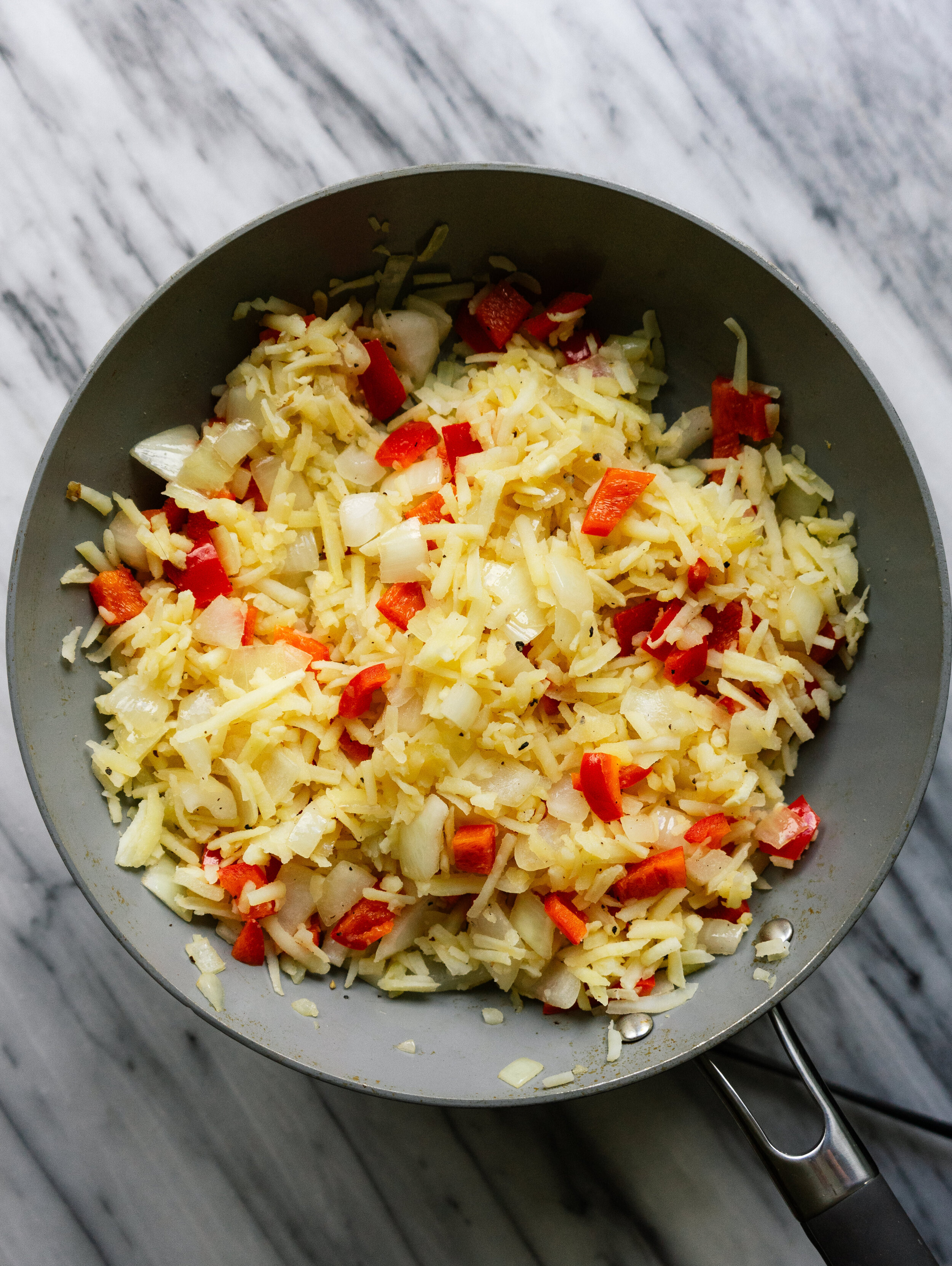 Above view of hash browns in a frying pan with onions and red bell peppers