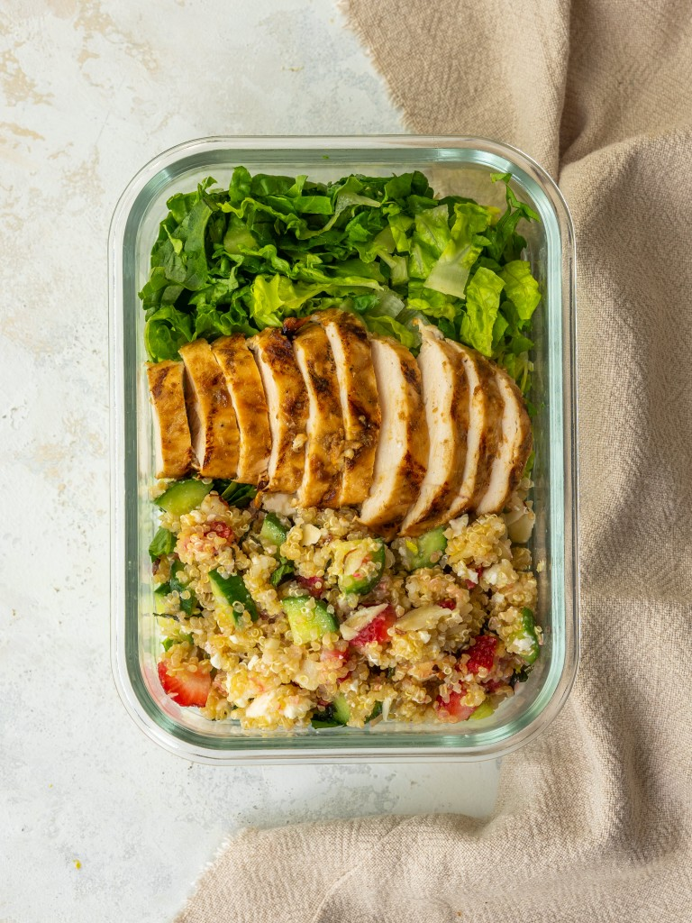 Above view of sliced balsamic chicken served on a green salad with quinoa
