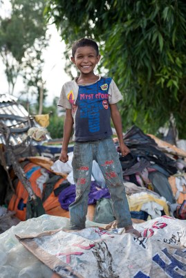This beaming boy lives on a rubbish dump with his family. What's so special about this photo? He was noticed.