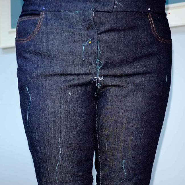 Jeans before fit adjustments showing wrinkles across the belly